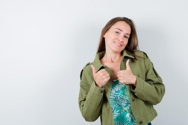 Porträt einer jungen dame, die doppelte daumen in grüner jacke zeigt und fröhliche vorderansicht sieht
