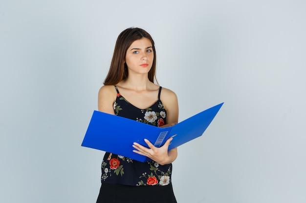 Porträt einer jungen dame, die einen geöffneten ordner in der bluse hält und nachdenkliche vorderansicht schaut