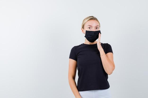 Porträt einer jungen dame, die hand auf maske in t-shirt, hose, medizinischer maske hält