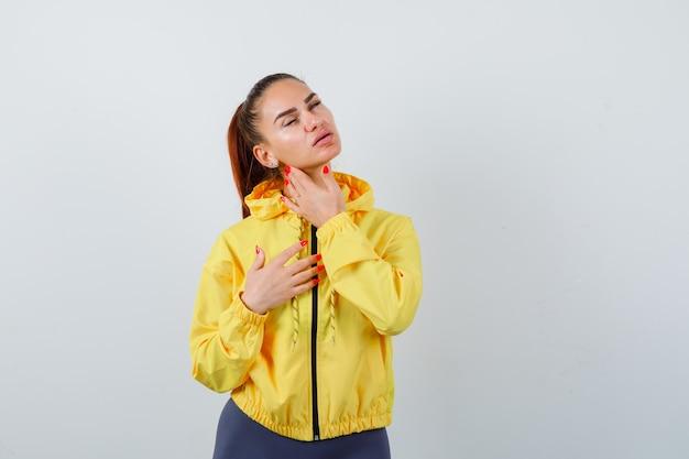 Porträt einer jungen dame, die ihre gesichtshaut in der gelben jacke berührt und eine charmante vorderansicht sieht