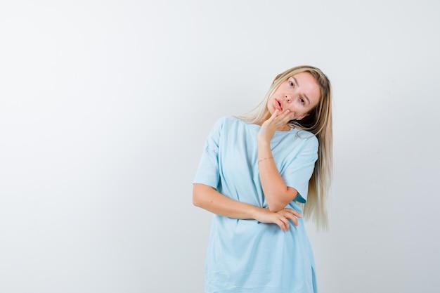 Porträt einer jungen dame, die im t-shirt die hand auf die wange hält und ziemlich isoliert aussieht