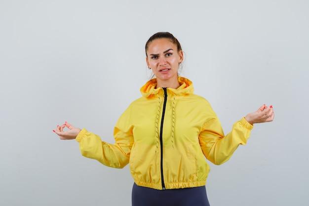 Porträt einer jungen dame, die im trainingsanzug meditiert und hoffnungsvolle vorderansicht schaut