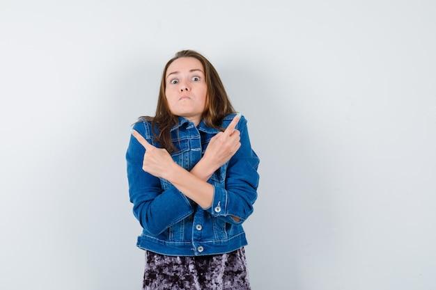 Porträt einer jungen dame, die in bluse, jeansjacke auf beide ecken zeigt und ernsthafte vorderansicht sieht