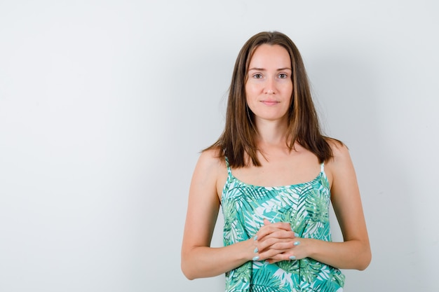 Porträt einer jungen dame, die in der bluse gefaltete hände vor sich hält und eine süße vorderansicht sieht