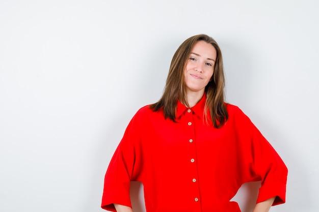 Porträt einer jungen dame, die in roter bluse die hände auf den hüften hält und fröhliche vorderansicht sieht