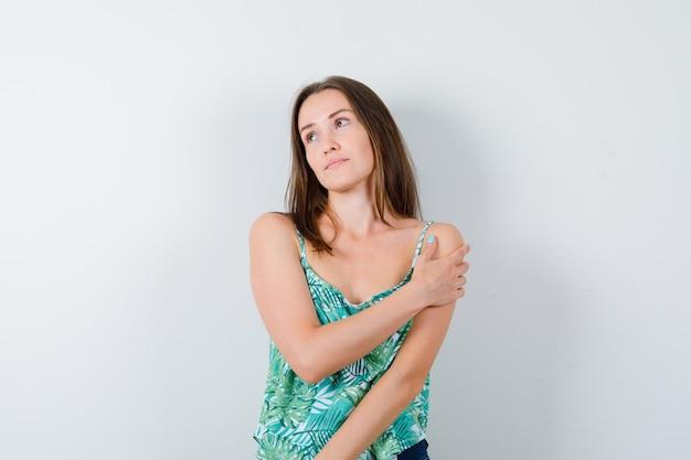 Porträt einer jungen dame, die mit der hand auf ihrem arm wegschaut und eine verträumte vorderansicht sieht
