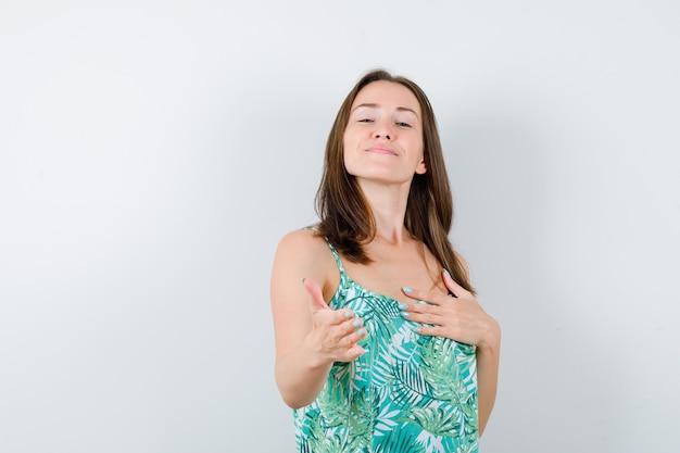 Porträt einer jungen dame, die sich die hand zum gruß in der bluse ausdehnt und eine süße vorderansicht sieht
