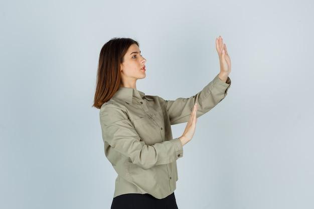 Porträt einer jungen dame, die versucht, sich mit den händen in hemd, rock und verängstigter vorderansicht zu blockieren