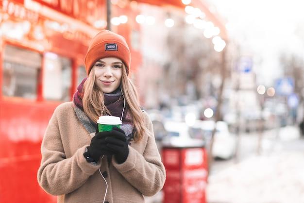 Porträt einer jungen dame in warmen kleidern und kopfhörern, auf dem hintergrund der straße stehend, pappbecher kaffee in ihren händen