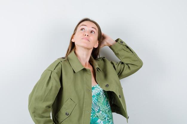 Porträt einer jungen dame mit hand hinter dem kopf in grüner jacke und nachdenklicher vorderansicht