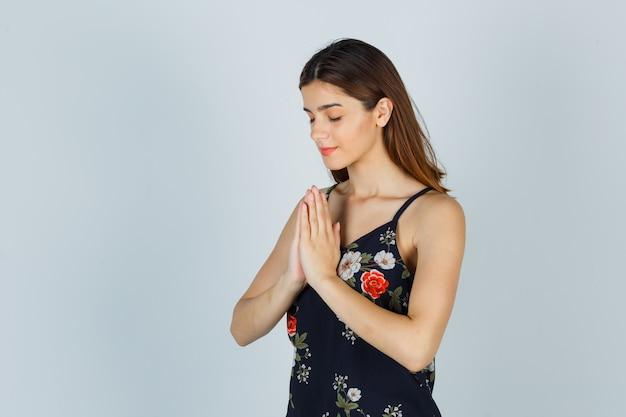 Porträt einer jungen dame mit namaste-geste in bluse und hoffnungsvoller vorderansicht