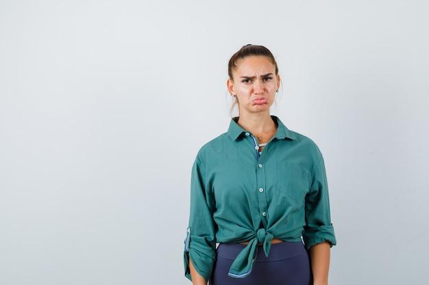 Porträt einer jungen dame mit stirnrunzeln, geschwungener unterlippe im grünen hemd und beleidigter vorderansicht