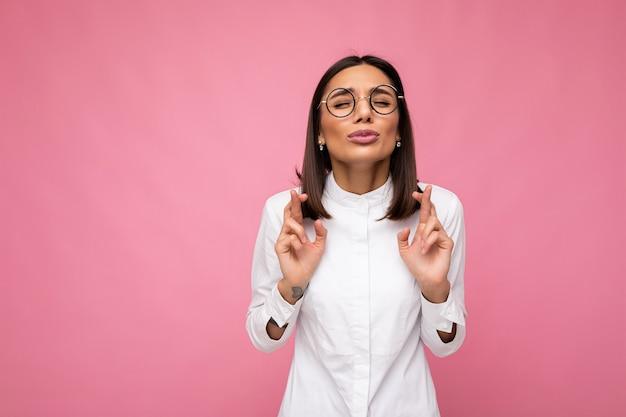 Porträt einer jungen emotionalen hübschen brünetten dame mit kurzem haarschnitt, die ein lässiges weißes hemd trägt und