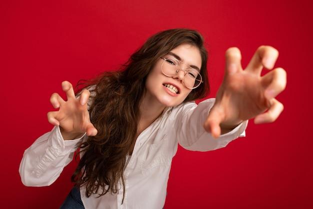 Porträt einer jungen emotionalen hübschen brünetten frau, die ein lässiges weißes hemd und eine optische brille trägt