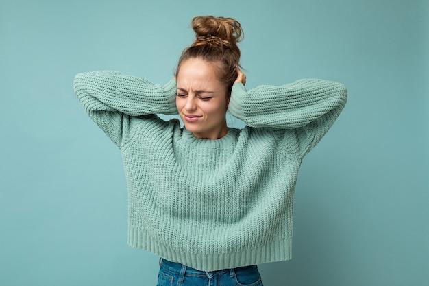 Porträt einer jungen emotionalen traurigen unzufriedenen attraktiven blonden frau mit aufrichtigen emotionen, die ein lässiges blaues trikot trägt, isoliert auf blauem hintergrund mit leerem raum und bedeckenden ohren