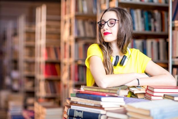 Porträt einer jungen enthusiastischen studentin, die mit vielen büchern in der bibliothek studiert