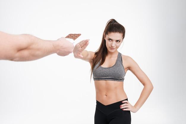 Porträt einer jungen entschlossenen fitnessfrau, die sich weigert, schokolade aus der hand zu nehmen, isoliert