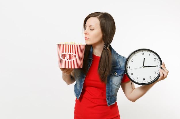 Porträt einer jungen entspannten, schönen brünetten frau in freizeitkleidung, die filmfilm sieht, eimer mit popcorn und wecker hält und auf weißem hintergrund schreit. emotionen im kinokonzept.