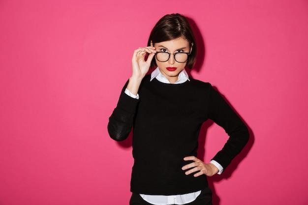 Porträt einer jungen ernsten geschäftsfrau in den brillen