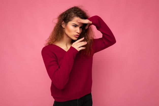 Porträt einer jungen, ernsten, schönen, brünetten, lockigen frau mit aufrichtigen emotionen, die trendiges pink trägt