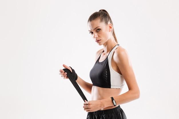Porträt einer jungen ernsthaften sportlerin, die ihre hände verbindet
