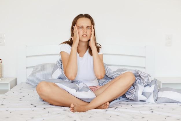 Porträt einer jungen erwachsenen frau, die weißes lässiges t-shirt trägt, mit gekreuzten beinen auf dem bett im schlafzimmer sitzt, schreckliche kopfschmerzen hat und die hände an ihren schläfen hält.
