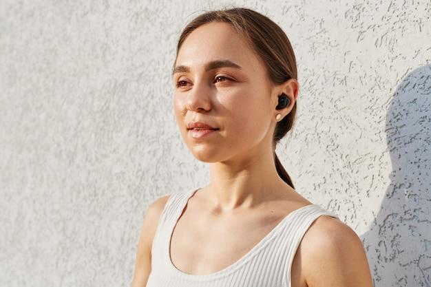 Porträt einer jungen erwachsenen frau mit angenehmem aussehen mit airpods, die mit verträumtem ausdruck wegschauen