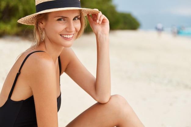 Porträt einer jungen europäischen frau mit perfekter figur, die mit sommerferien zufrieden ist, froh, freizeit am sandstrand im sommerwetter zu verbringen. attraktive weibliche posen auf tropischer insel