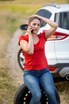 Porträt einer jungen fahrerin, die neben dem kaputten auto sitzt und telefoniert