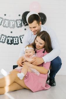 Porträt einer jungen familie mit einem einjährigen mädchen in seinen armen. babys erster geburtstag