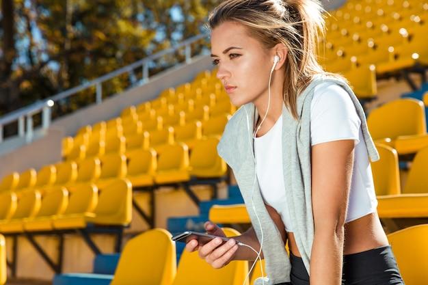 Porträt einer jungen fitnessfrau, die smartphone auf stadion im freien hält