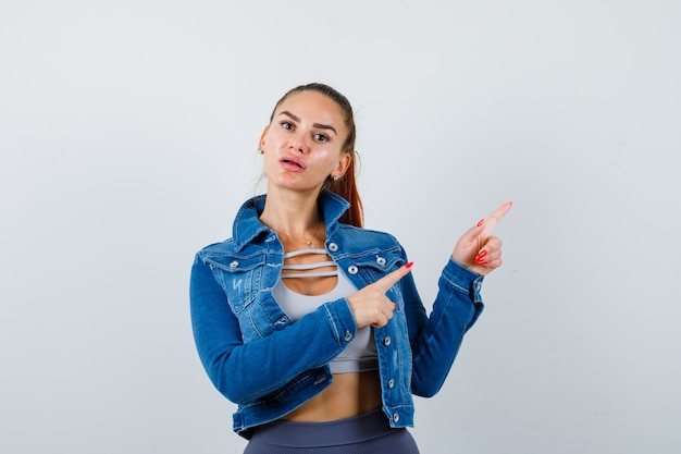Porträt einer jungen, fitten frau, die auf die obere rechte ecke zeigt, jeansjacke und freudlose vorderansicht