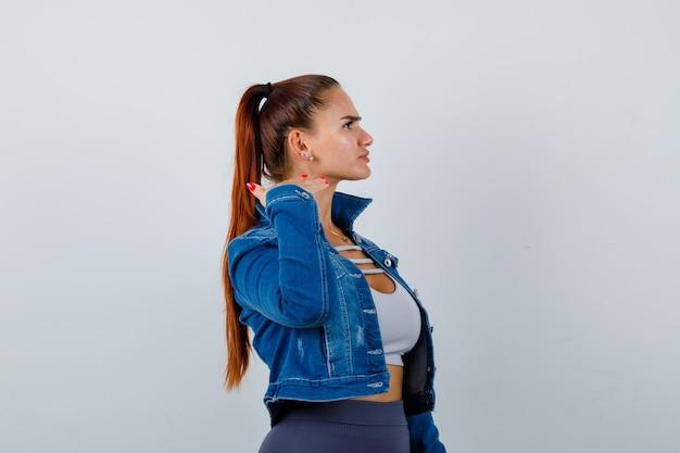 Porträt einer jungen, fitten frau, die die haut am hals mit den fingern im oberteil berührt, jeansjacke und aggressiv aussieht
