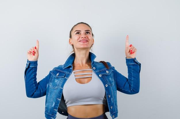 Porträt einer jungen, fitten frau, die oben in der jeansjacke nach oben zeigt und eine glückselige vorderansicht sieht