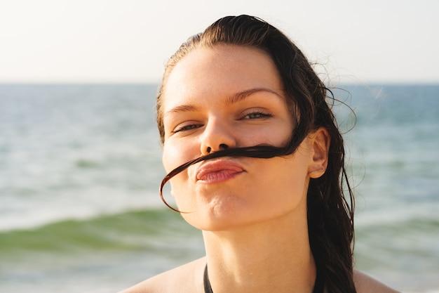 Porträt einer jungen frau am strand, die schnurrbart gemacht