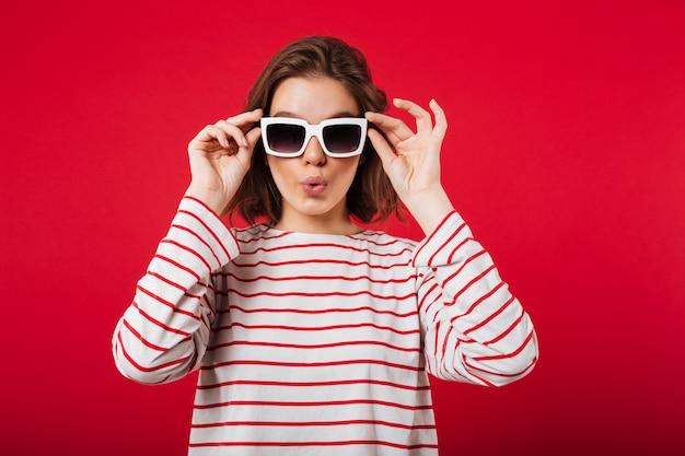 Porträt einer jungen frau bei der sonnenbrilleaufstellung