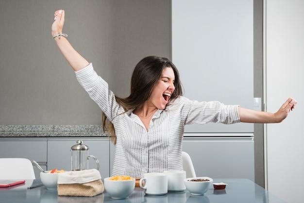 Porträt einer jungen frau, die am frühstückstische ausdehnt ihre arme sitzt