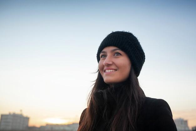 Porträt einer jungen frau, die am strand mit winterkleidung lacht.