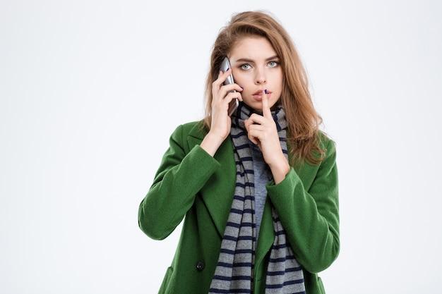 Porträt einer jungen frau, die am telefon spricht und finger über die lippen zeigt, isoliert auf weißem hintergrund