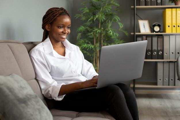 Porträt einer jungen frau, die an ihrem laptop in einem startup-unternehmen arbeitet