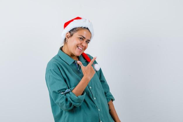 Porträt einer jungen frau, die auf die obere rechte ecke in hemd, weihnachtsmütze zeigt und freudige vorderansicht schaut
