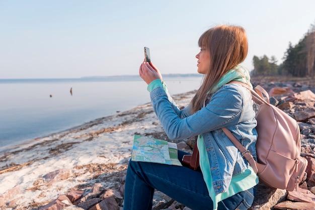 Porträt einer jungen frau, die auf strand mit karte unter verwendung des handys sitzt