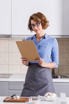 Porträt einer jungen frau, die das rezept auf klemmbrett in der küche liest
