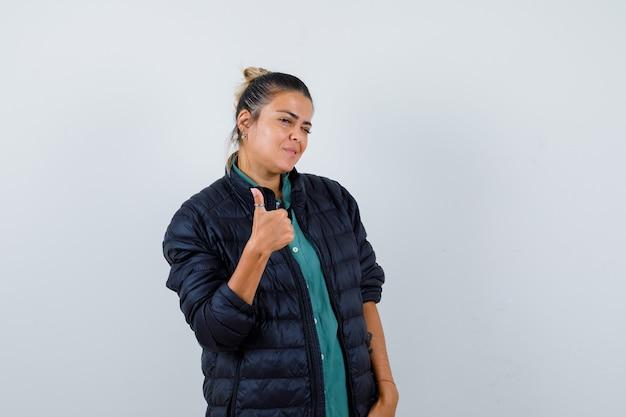 Porträt einer jungen frau, die den daumen im hemd, der daunenjacke und der glücklichen vorderansicht zeigt