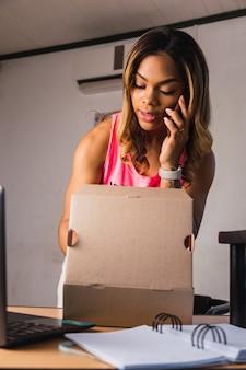 Porträt einer jungen frau, die die box mit produkten für die lieferung vorbereitet.
