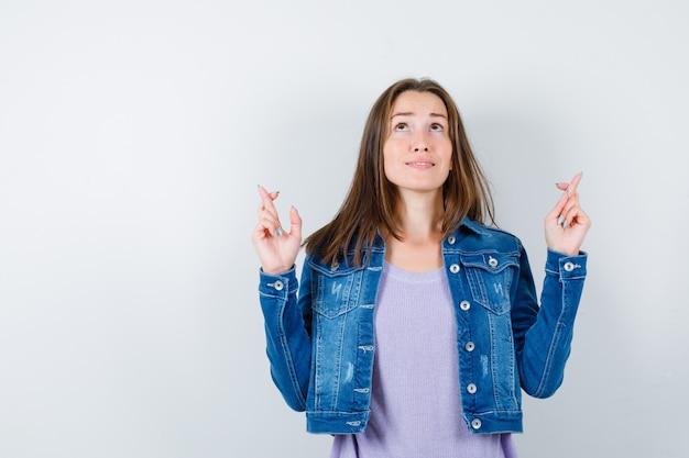 Porträt einer jungen frau, die die daumen drückt, in t-shirt, jacke und hoffnungsvoller vorderansicht aufschaut