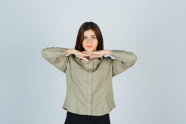 Porträt einer jungen frau, die die hände unter dem kinn in hemd, rock hält und vernünftige vorderansicht sieht