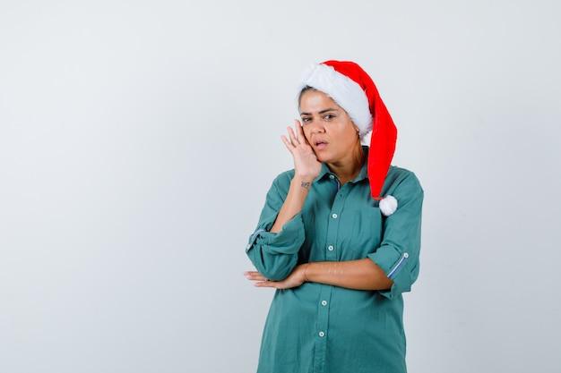 Porträt einer jungen frau, die die hand auf die wange im hemd hält, weihnachtsmütze und interessierte vorderansicht schaut