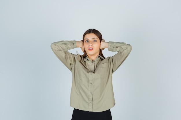 Porträt einer jungen frau, die die ohren mit den händen in hemd, rock bedeckt und verängstigte vorderansicht schaut