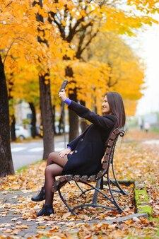Porträt einer jungen frau, die ein selfie im herbstpark nimmt